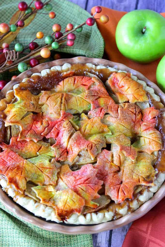 Vertical image of an apple pie with autumn leaves and apples.