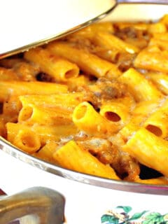 A casserole dish filled with pumpkin cream pasta with bratwurst and a small pumpkin on the side.