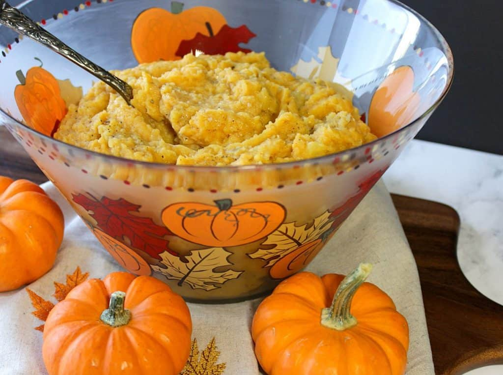 A large glass bowl of pumpkin mashed potatoes with mini pumpkins and leaves painted around the bowl.