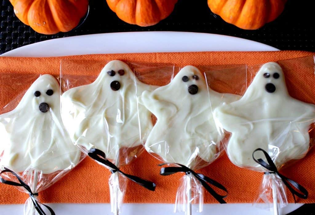 Overhead photo of 4 White Chocolate Ghost Pops on a white plate with an orange napkin and 3 small pumpkins.
