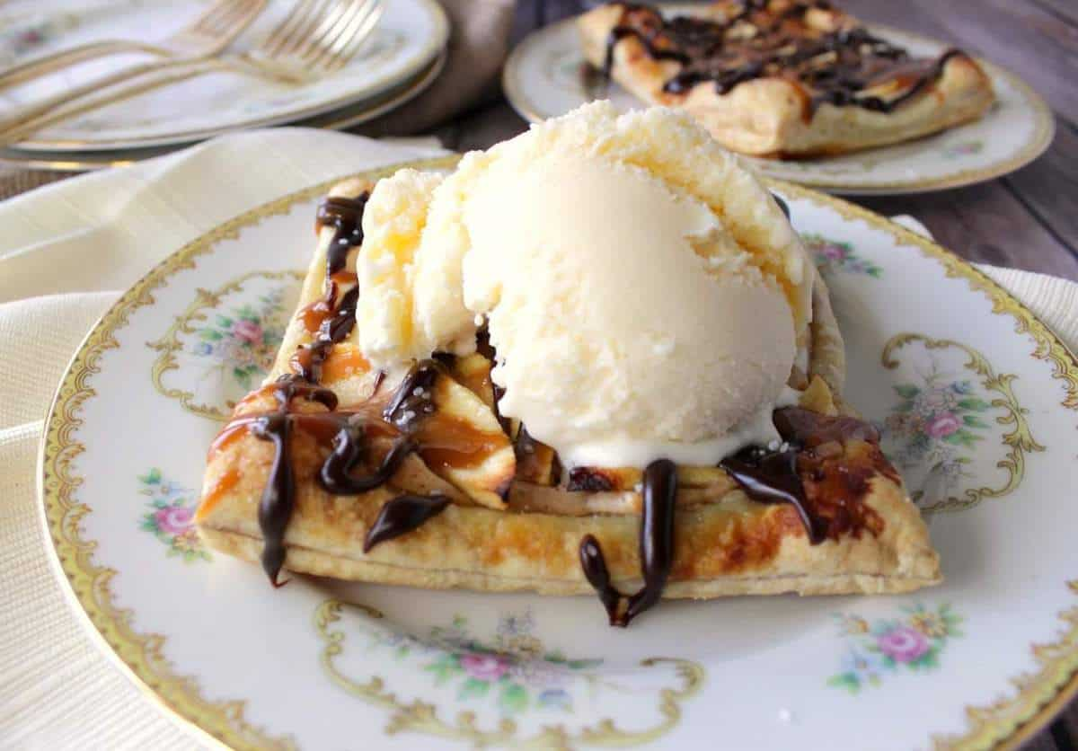 A Puff Pastry Apple Square on a china plate with a scoop of vanilla ice cream on top.