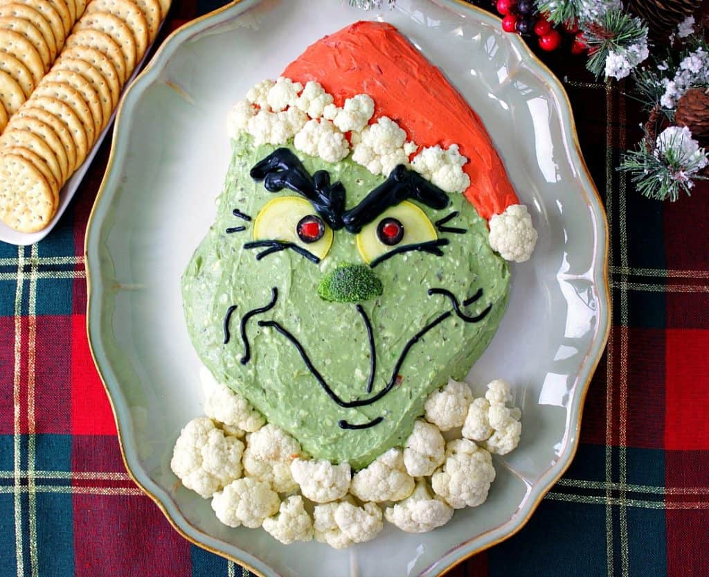 Grinch guacamole on a platter with cauliflower fur and crackers.
