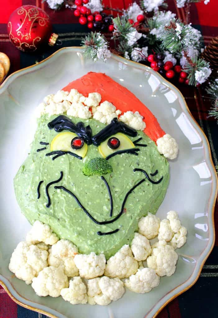 Vertical overhead photo of Grinch guacamole on an oval platter with cauliflower fur and a broccoli nose.