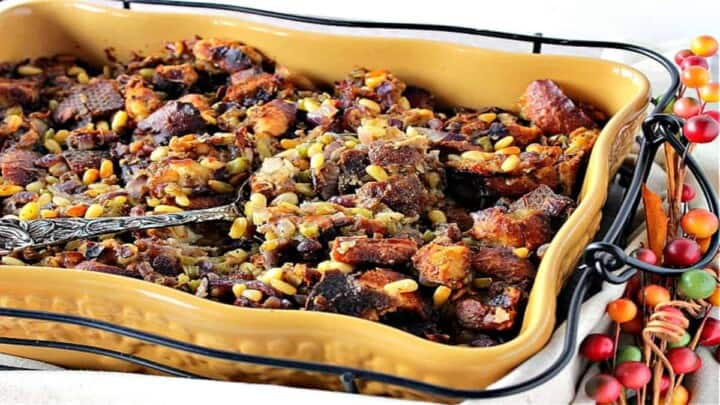 A mustard yellow casserole dish filled with Pretzel Roll Stuffing along with a serving spoon.