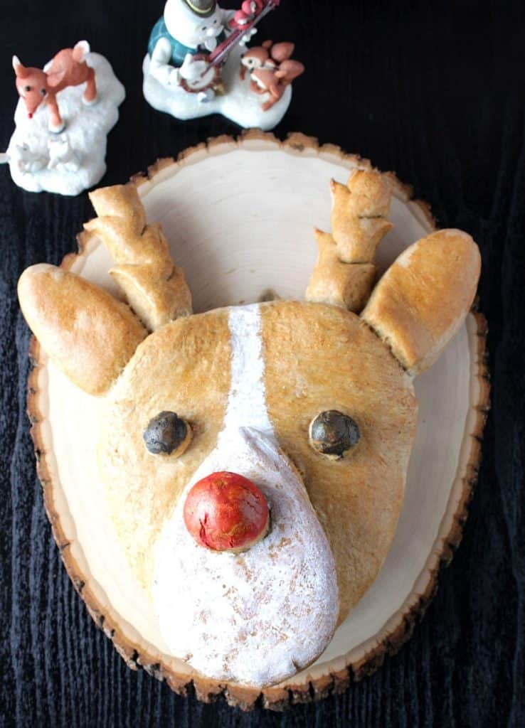 Vertical Overhead Rudolph bread on a black background with two Rudolph statutes in the background.