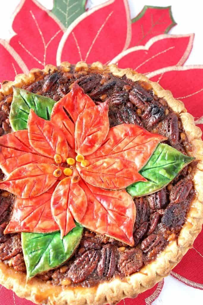 Vertical overhead closeup photo of a pecan pie with a painted poinsettia crust on top. Christmas dinner recipe roundup.