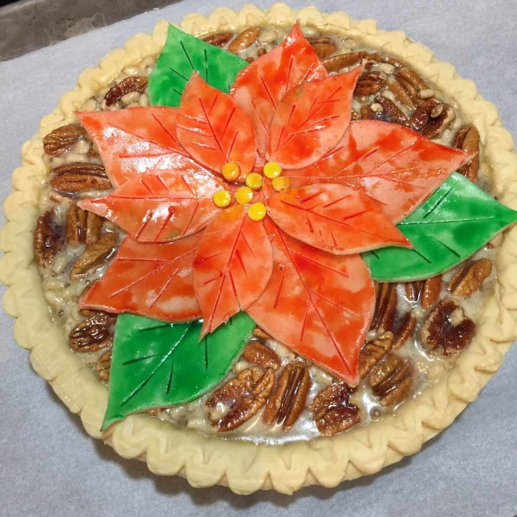 A square photo of an unbaked painted poinsettia pie with red and green leaves.