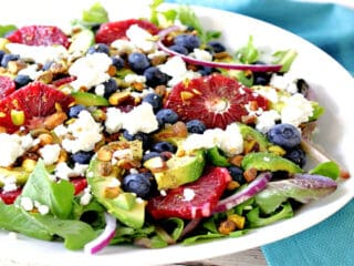 An offset horizontal photo of a Blood Orange Salad in a white bowl with blueberries, avocados, pistachios and feta cheese.