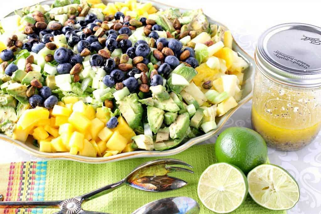 A horizontal photo of an avocado and mango salad on a platter with limes, tongs, and a jar of homemade vinaigrette on the side.