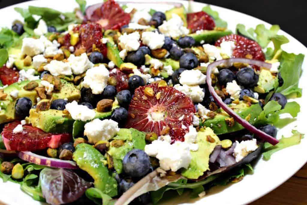 Salad on a white plate featuring blood oranges, blueberries, and feta cheese