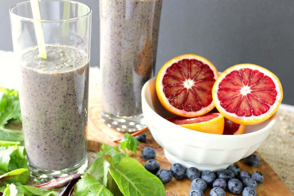 2 blood orange blueberry breakfast smoothies with a bowl of blood oranges, blueberries and lettuces