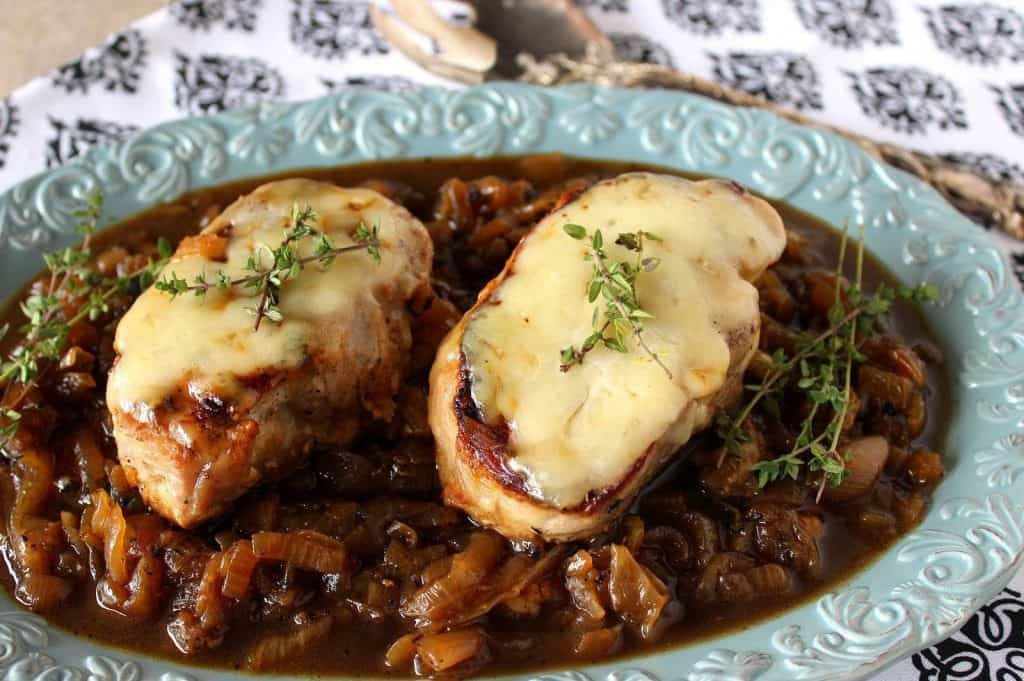 Two juicy French onion pork chops on a pretty blue plate with cheese, caramelized onions and fresh thyme sprigs.