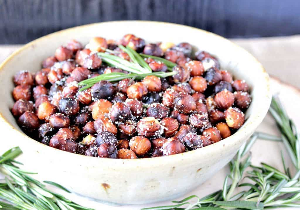 A white bowl filled with Roasted Rosemary Hazelnuts with fresh rosemary for garnish