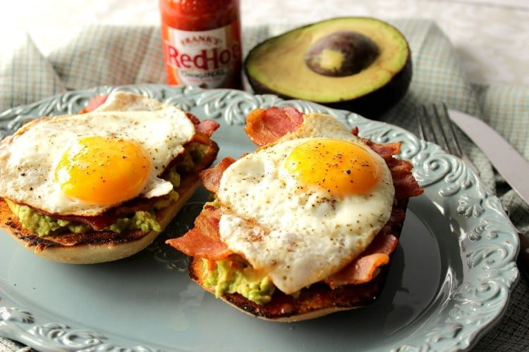 Two servings of Avocado Toast with Bacon and Egg on a blue plate with hot sauce and an avocado half in the background.
