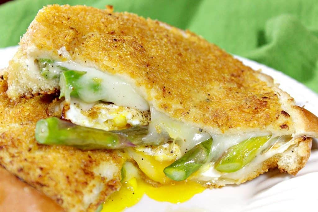 Closeup picture of a melted grilled cheese sandwich with asparagus and a runny egg.