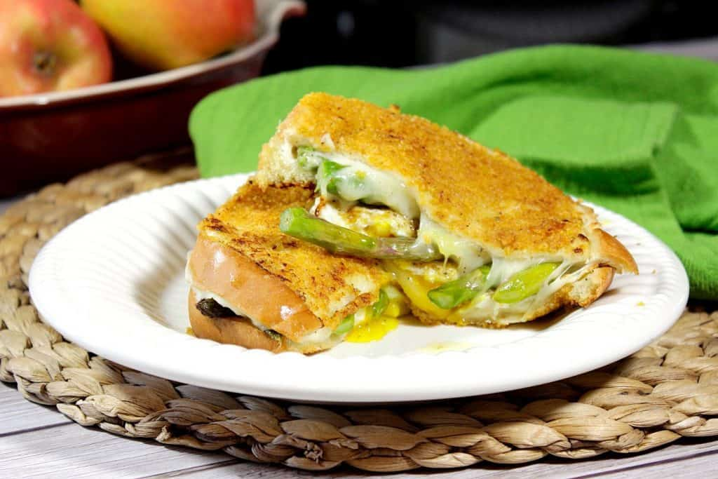 Grilled cheese breakfast sandwich on a white plate with a green napkin and apples in the background.