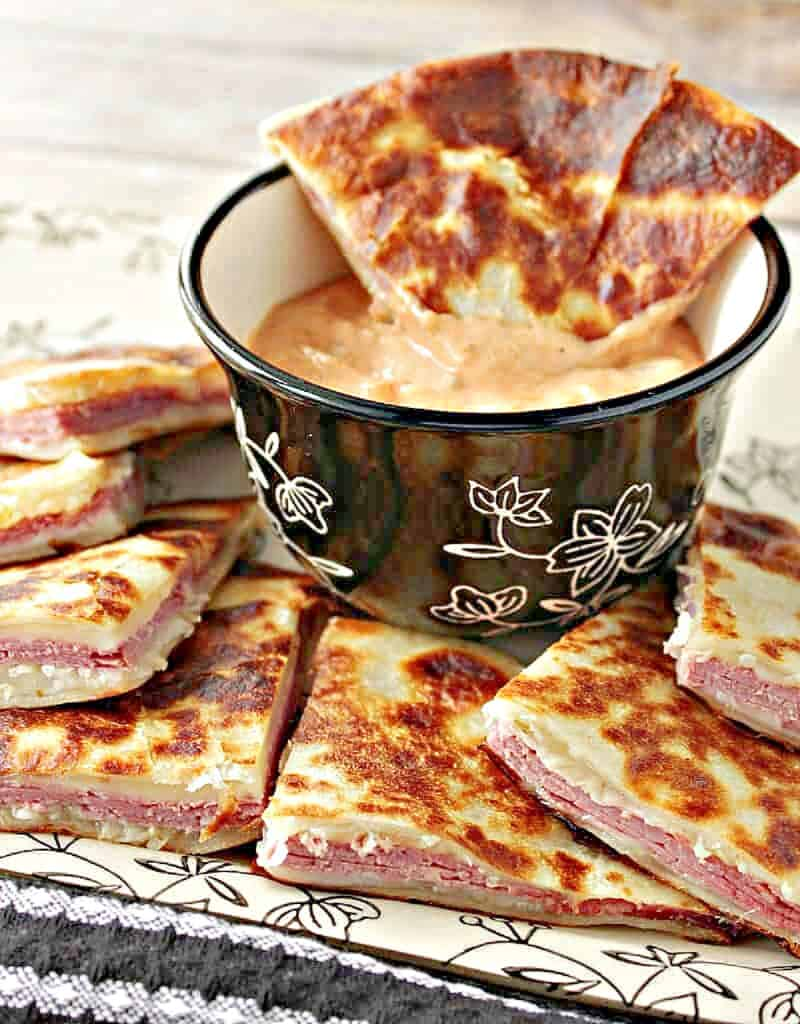 A vertical closeup of Reuben Quesadillas cut into triangles along with a center cup of 1000 Islands dipping sauce.