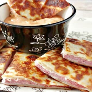 A black and white tray filled with Reuben Quesadillas with a center cup of dipping sauce.