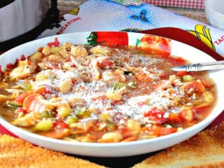 A bowl filled with Italian Pepperoni Soup with a spoon and toast slices in the foreground
