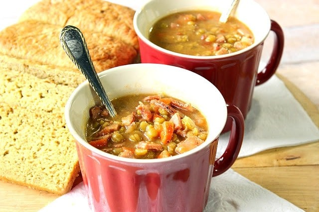 Slow Cooker Split Pea Soup with Ham in two red mugs with spoons