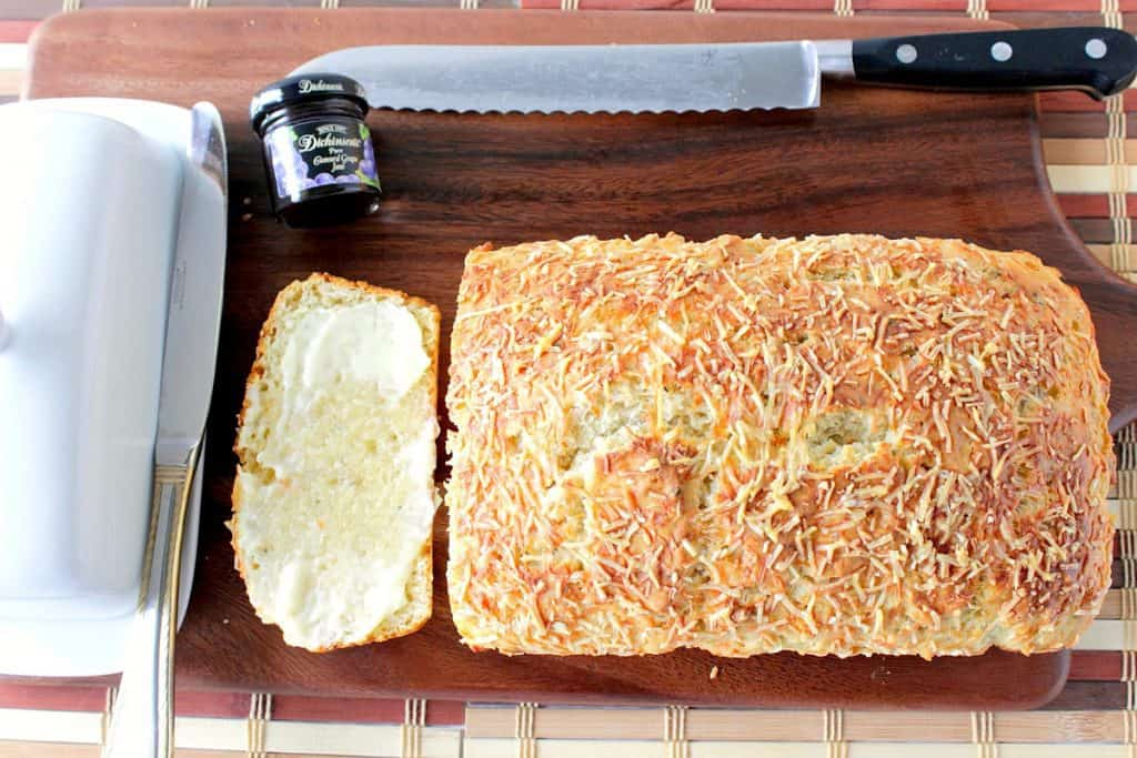 Overhead picture of Savory Quick Bread with butter, jam, and a serrated knife on a cutting board.