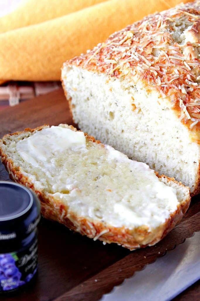 A vertical closeup photo of a sliced loaf of savory quick bread with melted butter.