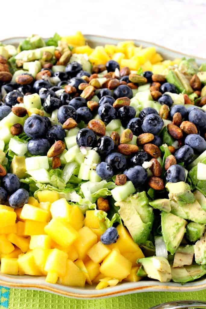 Closeup photo of an avocado mango salad with blueberries and pistachios.