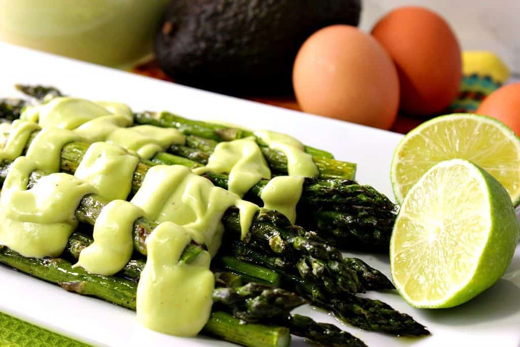 Oven Roasted Asparagus with Creamy Avocado Hollandaise Sauce over top. BBQ side dish.