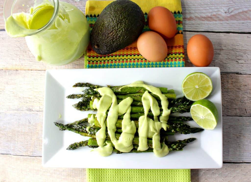 Overhead photo of a plate of asparagus topped with avocado hollandaise sauce.