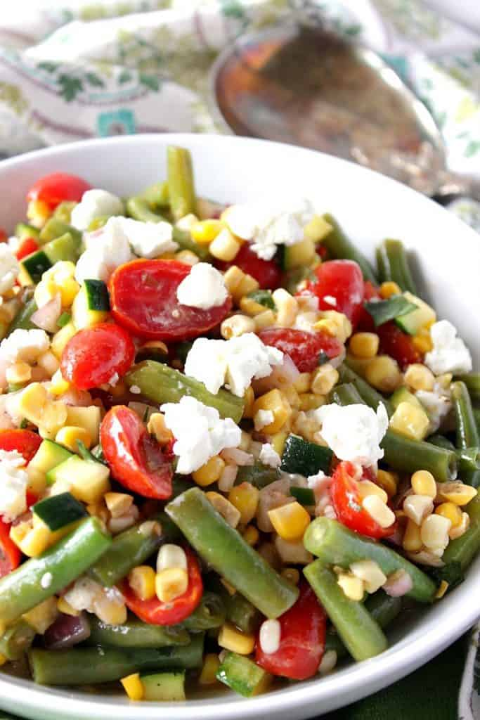 Closeup photo of Farmer's Market Veggie Salad in a white bowl with goat cheese and tomatoes.