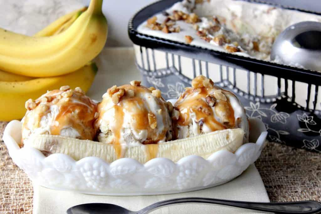 Three scoops of No Churn Banana Walnut Ice Cream in a sundae dish with caramel and bananas