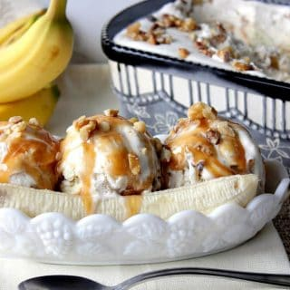 No Churn Banana Walnut Ice Cream in a ice cream dish with bananas and caramel sauce.