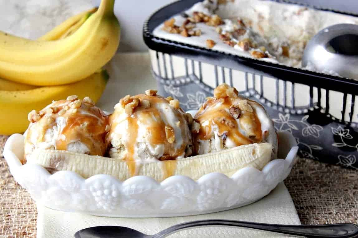 No Churn Banana Walnut Ice Cream in a ice cream dish with bananas and caramel sauce.