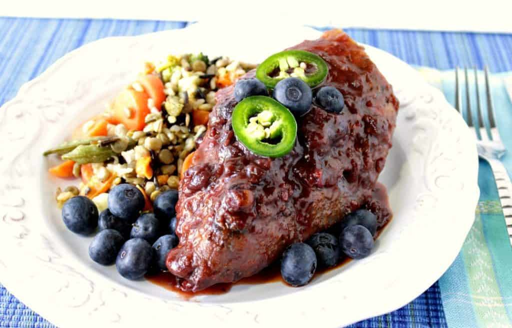 Blueberry Chicken Chile Skillet Dinner with Fresh Blueberries and Jalapeno on a white dinner plate with a blue napkin