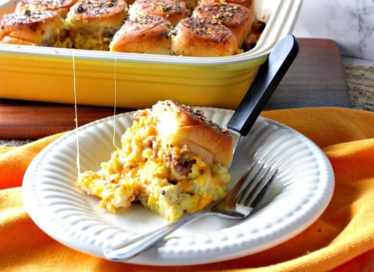 A breakfast slider with scrambled eggs and sausage on a white plate with a casserole dish in the background.