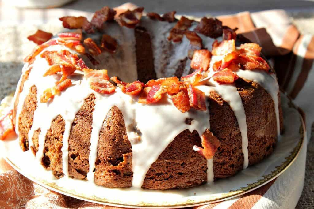 a horizontal photo of a bundt cake with white icing and bacon on top.