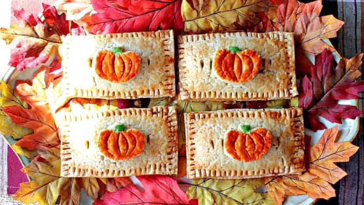 A direct overhead horizontal photo of four Pumpkin Hand Pies on a platter with autumn leaves surrounding the pies.