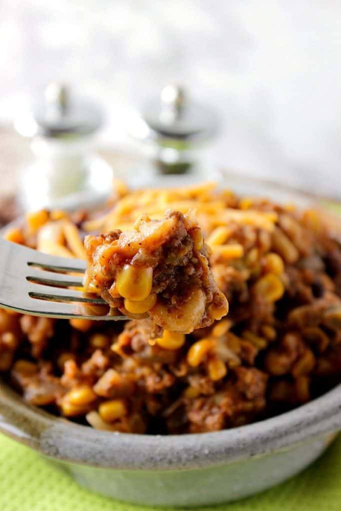 Closeup vertical image of slow cooker chili mac on a fork with corn.