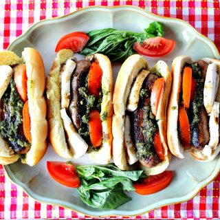 Overhead photo of 4 Caprese Sausage Sandwiches on a platter with a red and white checkered napkin.