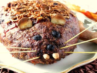 A horizontal photo of a Rat Loaf Meatloaf on a platter with almond teeth, spaghetti whiskers, olive eyes, and potato ears.