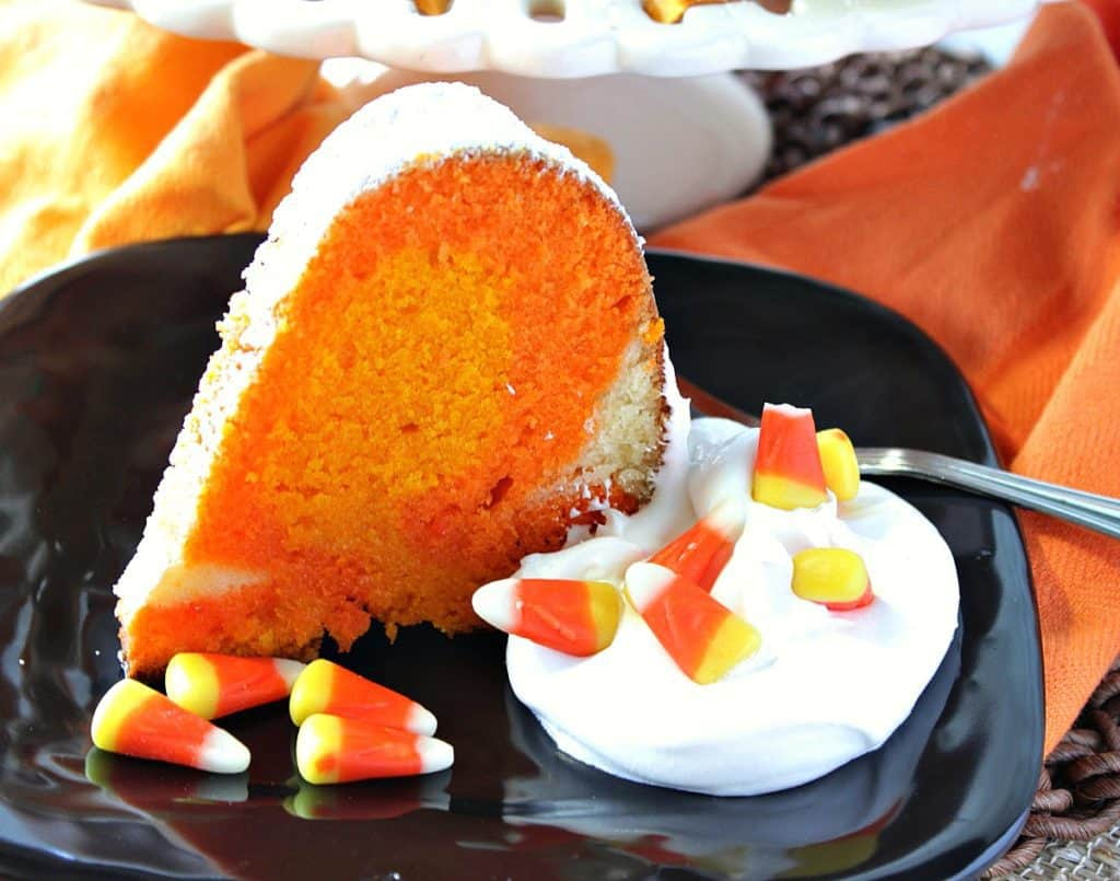 A horizontal photo of a slice of candy corn colored pound cake on a black plate with whipped cream and candy corn.
