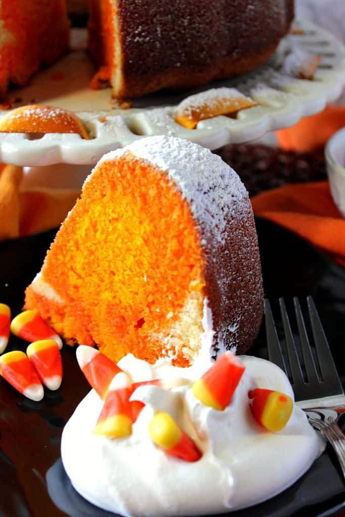 A closeup vertical photo of a slice of candy corn colored pound cake on a plate with whipped cream and candy corn.