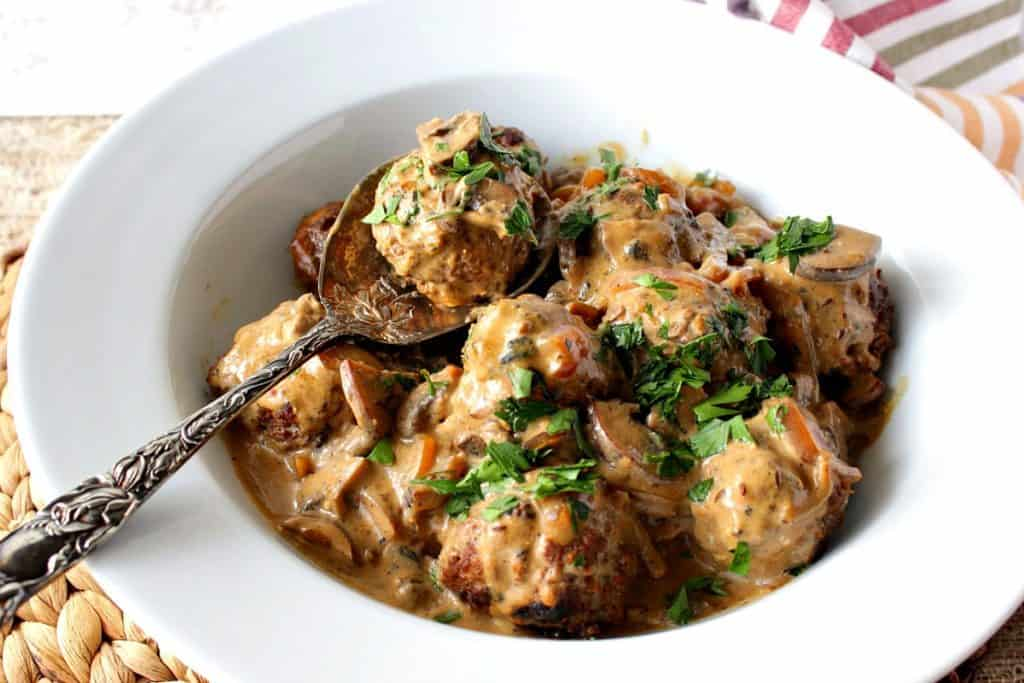 A white bowl filled with German meatballs, cream sauce, parsley, and a spoon.