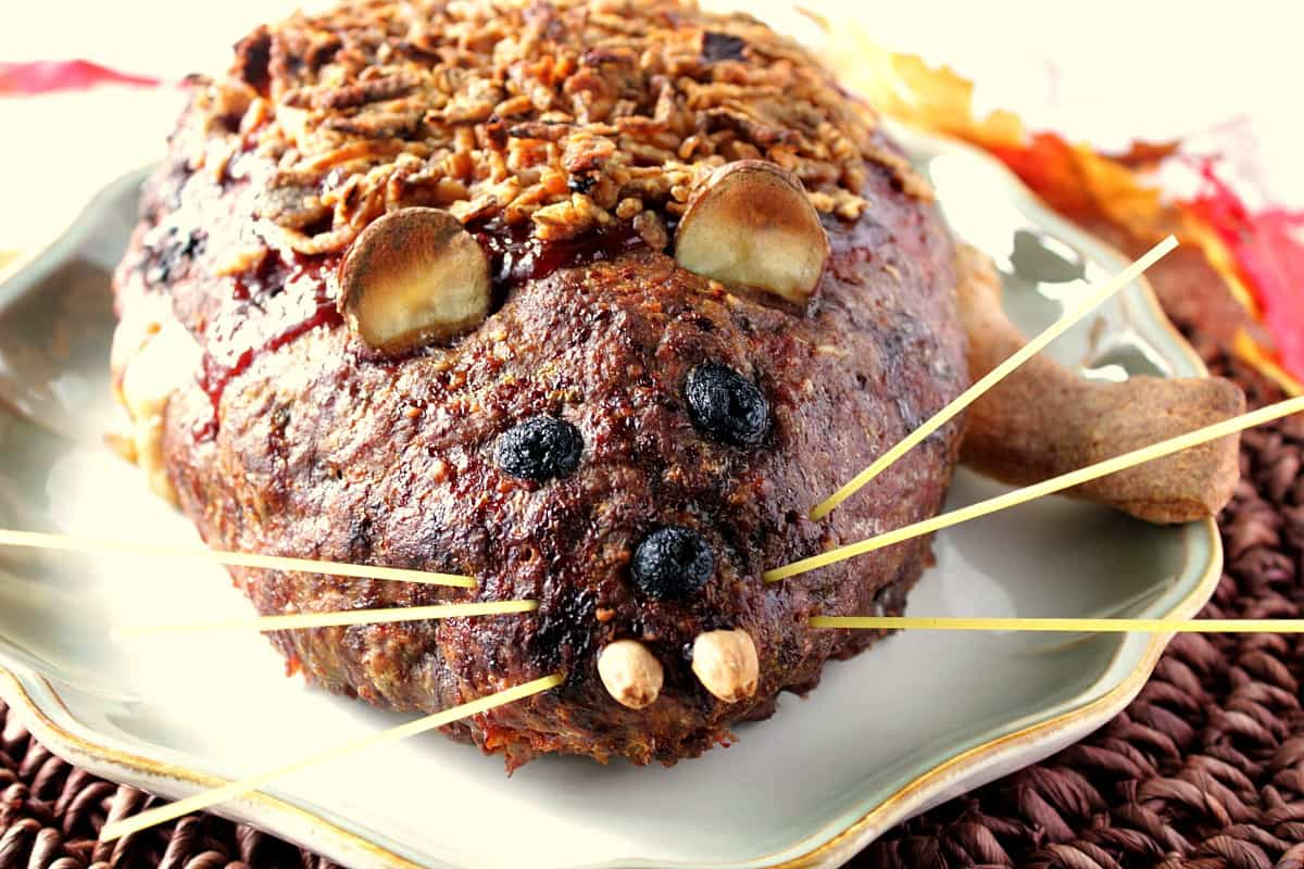 Face view of a rat loaf meatloaf on a plate with potato ears and spaghetti whiskers.