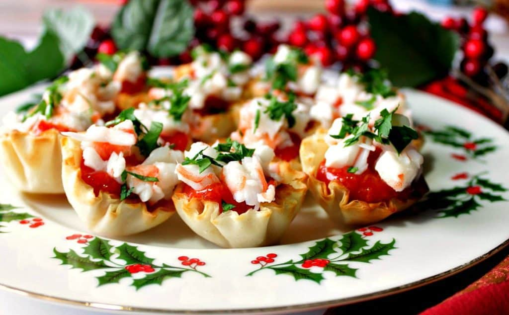 A plate filled with shrimp cocktail appetizer bites with cocktail sauce and parsley.