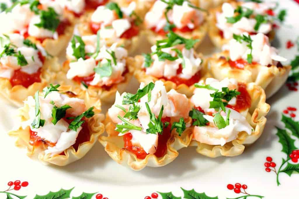 Festive Shrimp Cocktail Appetizer Bites with Homemade Cocktail Sauce on a holly berry platter with fresh parsley