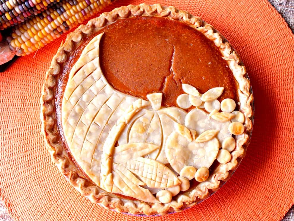 Overhead photo of a plain cornucopia pie with Indian corn on a orange place mat.