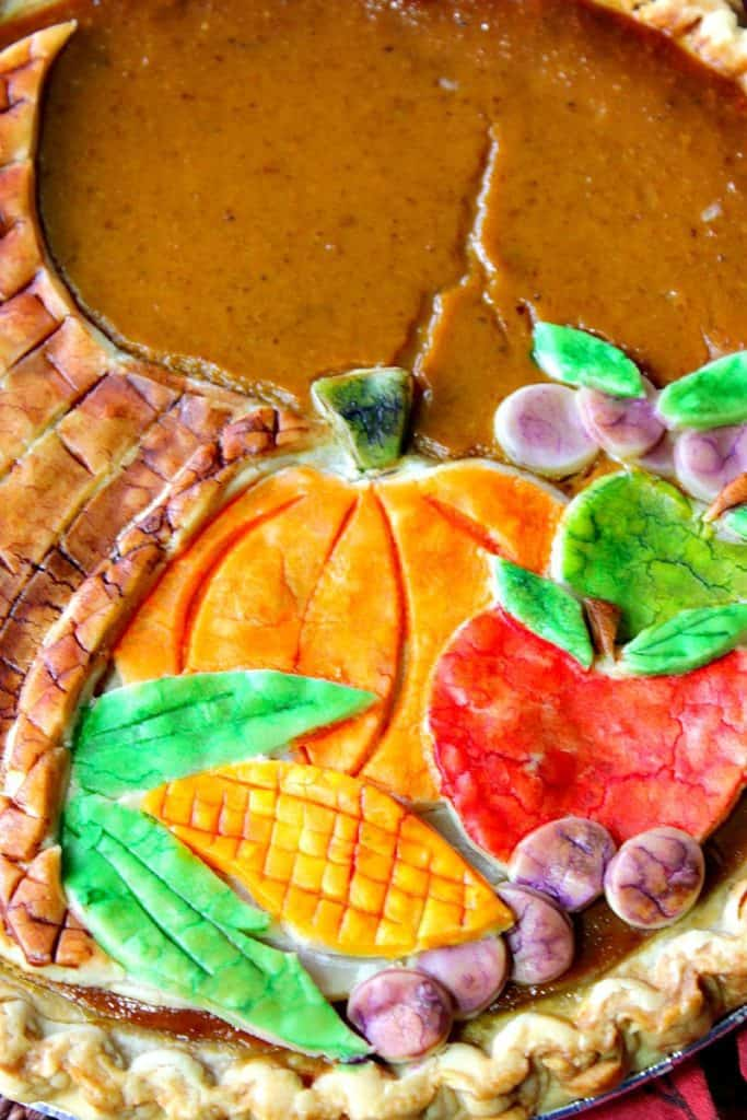 Closeup vertical image of a painted cornucopia pie crust on a pumpkin pie.