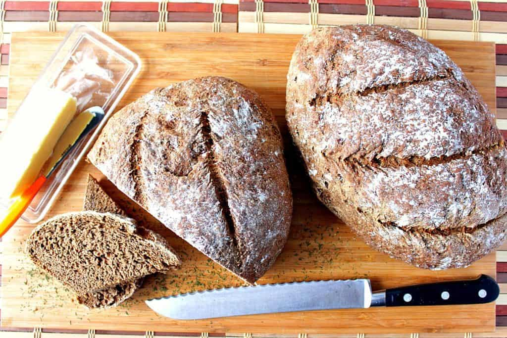 Overhead photo of two loaves of Onion Rye Bread with Dill along with a serrated knife and a butter dish.