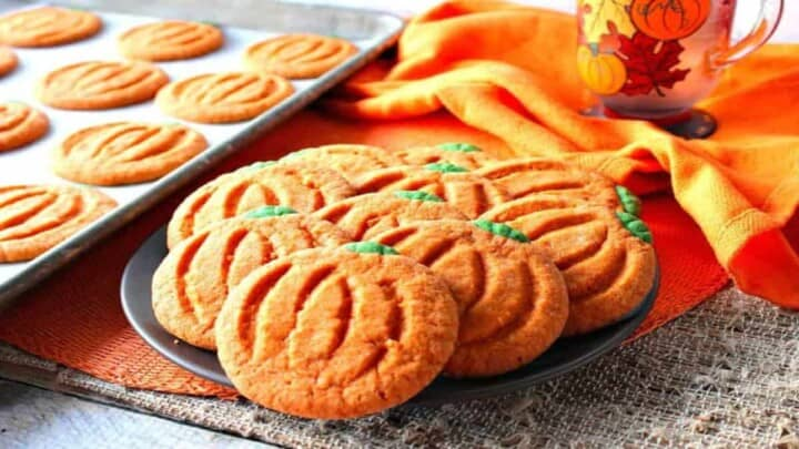 A plate filled with pumpkin-shaped sugar cookies in the foreground with a baking sheet and cookies in the background.